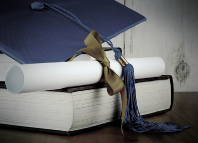 A blue graduation cap resting on two books with a diploma tied with gold ribbon on a wooden background. Copy space. Vintage filter added